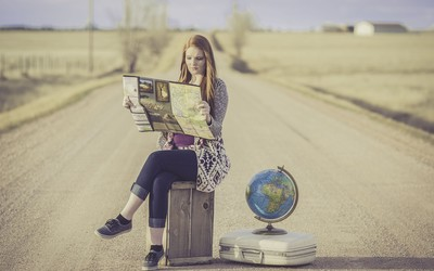 A 'globe trotter' - a lady sits on a a suitcase in the middle of a road reading a map with a globe at her side