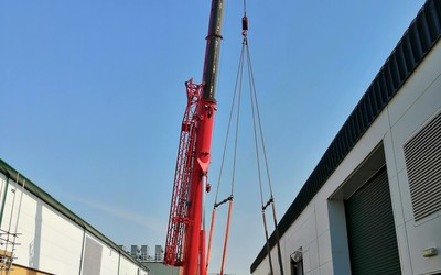 Crane delivering equipment for construction of Datum's upper floor facility